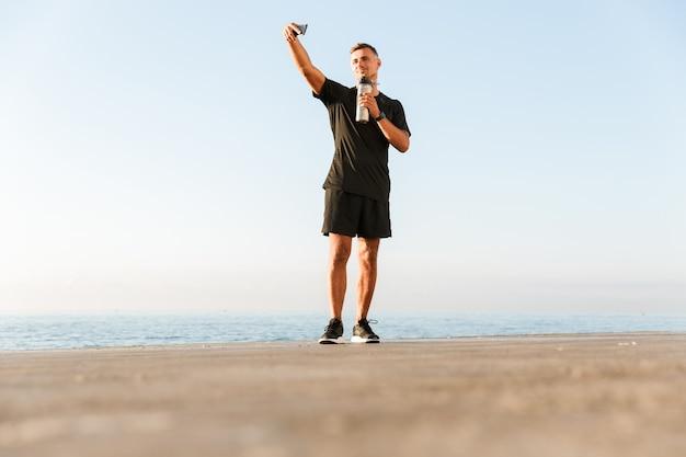 Sportivo maturo prendere un selfie con una bottiglia d'acqua sulla spiaggia.