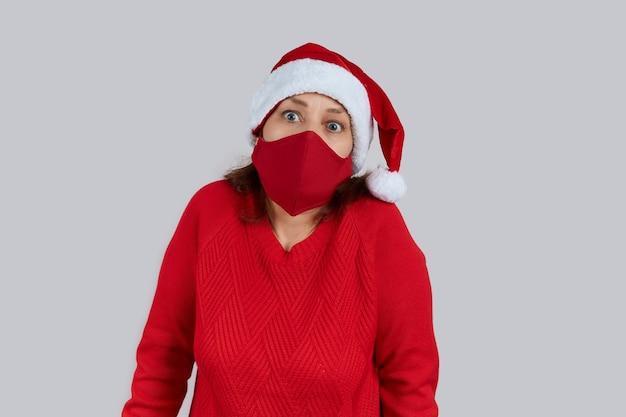Donna matura sorpresa in una maschera protettiva rossa, in un cappello da babbo natale su uno sfondo grigio. natale, capodanno in quarantena.
