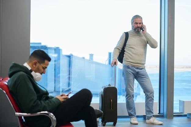 Viaggiatore maturo che parla al telefono cellulare mentre sta in piedi con i bagagli in sala d'attesa e viaggia in aereo