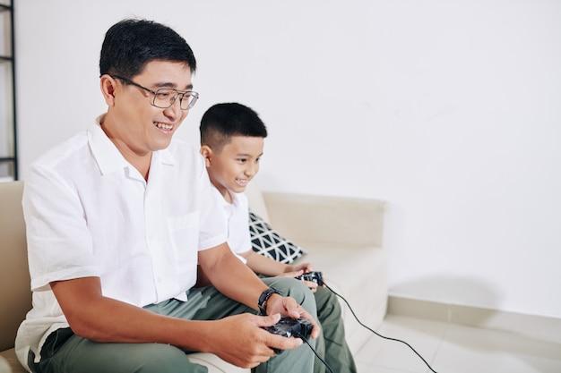 Uomo vietnamita maturo che si diverte a giocare al videogioco con suo figlio preadolescente a casa