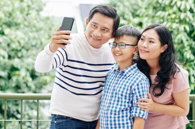 Coppia vietnamita uomo prendendo selfie con moglie e figlio preadolescente sul balcone