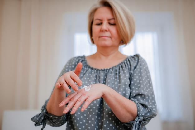 La donna matura applica una crema cosmetica idratante antietà alle mani, sorride a una donna di mezza età con una cura della pelle morbida e pulita e bellezza