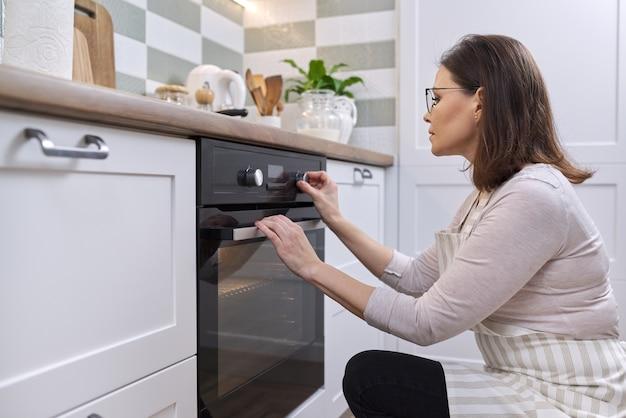 Donna matura in grembiule vicino al forno in cucina