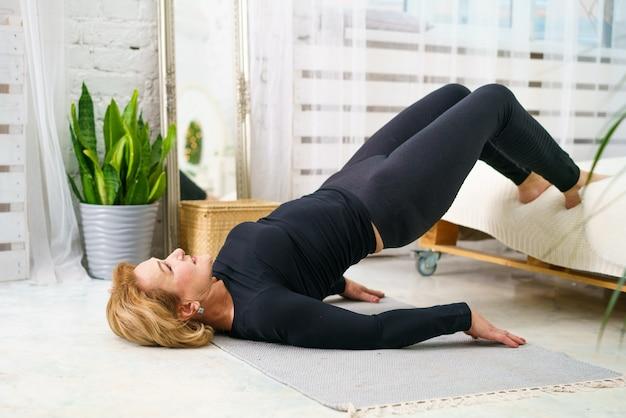 Una donna matura in abiti sportivi neri aspetto europeo facendo pilates a casa