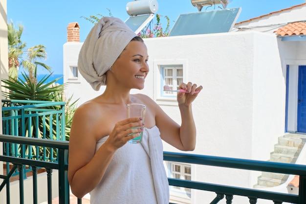 Donna matura si lava i denti, femmina con spazzolino da denti bicchiere d'acqua in telo da bagno sul balcone esterno, soleggiata giornata estiva al resort