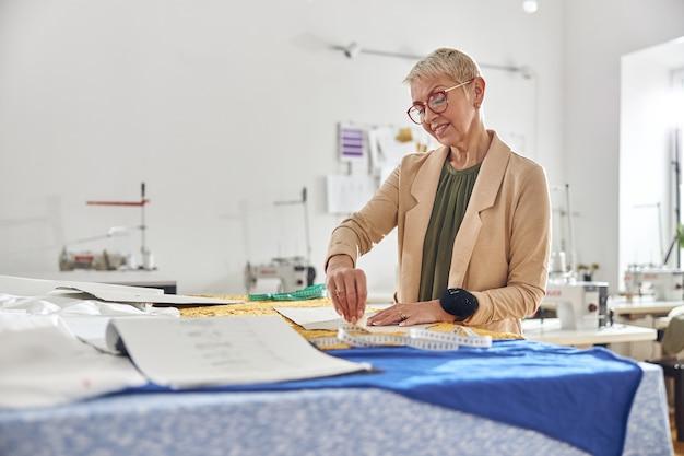 La designer donna matura disegna un motivo su tessuto a colori su un grande tavolo da taglio in officina
