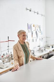 Donna matura designer con metro a nastro si trova al tavolo da taglio nel laboratorio di cucito