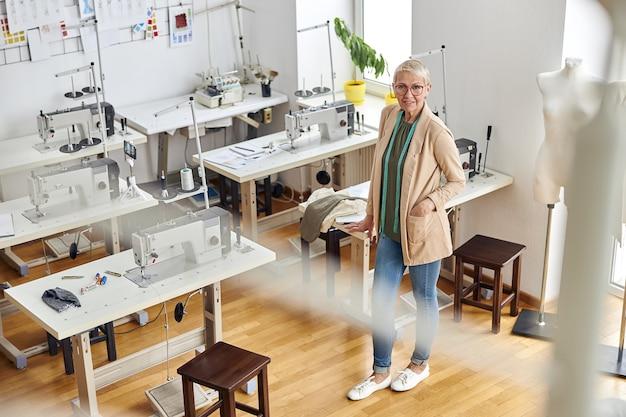 L'imprenditrice matura in abiti eleganti si trova in un laboratorio di cucito vuoto