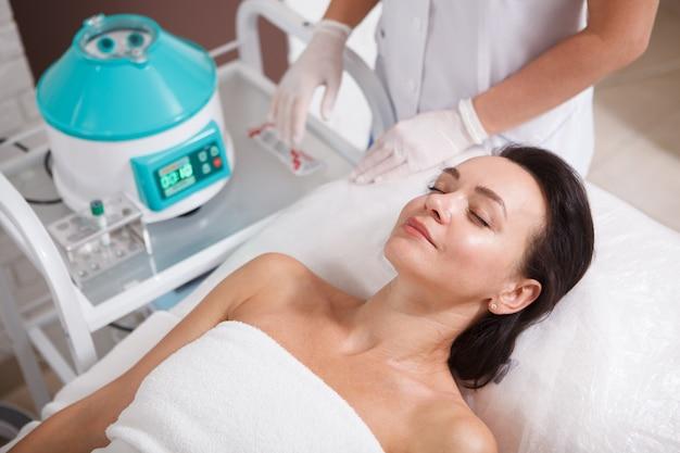 Donna matura che riceve terapia facciale prp da un cosmetologo professionista presso la clinica
