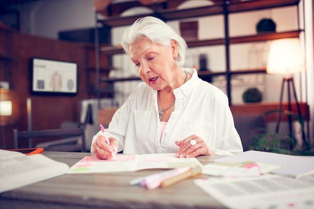 Donna matura. donna matura dai capelli grigi con un bel trucco che prende appunti mentre è seduta al tavolo