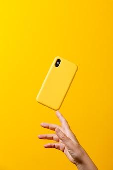 Mano di una donna matura che tiene uno smartphone giallo con una custodia gialla con un dito su uno sfondo giallo yellow