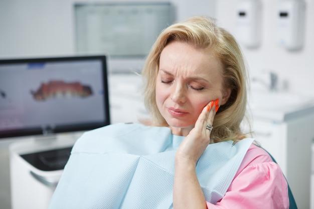 Donna matura che ha mal di denti, seduta sulla poltrona del dentista