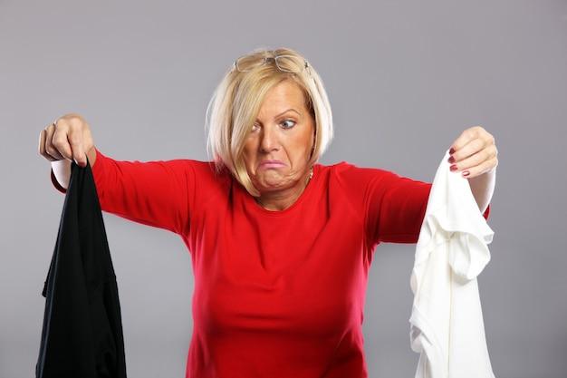 Una donna matura che tiene i vestiti sporchi sopra il grigio