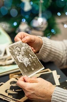 Donna matura che tiene in mano una foto della sua infanzia. i valori della famiglia concetto.