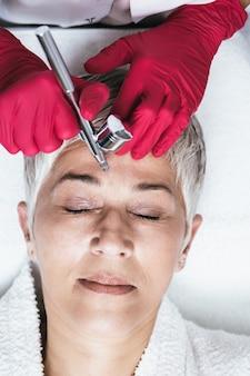 La donna matura sta ricevendo iniezioni facciali ringiovanenti. lei è sdraiata tranquillamente in clinica. l'estetista esperta sta iniettando il botox nelle rughe della donna.