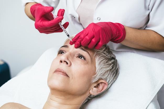 La donna matura sta ricevendo iniezioni facciali ringiovanenti. lei è sdraiata tranquillamente in clinica.