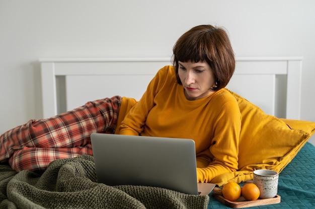 Donna matura posa sul letto in camera da letto e guardare film sul computer portatile. lavoro da casa, apprendimento a distanza, navigazione in internet la mattina dopo il risveglio.