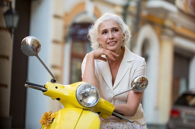 La donna matura si appoggia al motorino.