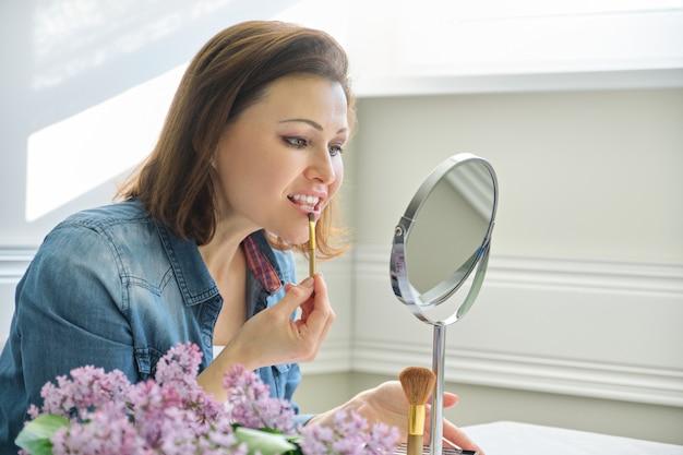 Donna matura che guarda il suo viso nello specchio, facendo il trucco