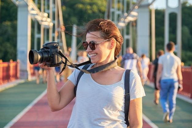 Donna matura che fotografa con la macchina fotografica