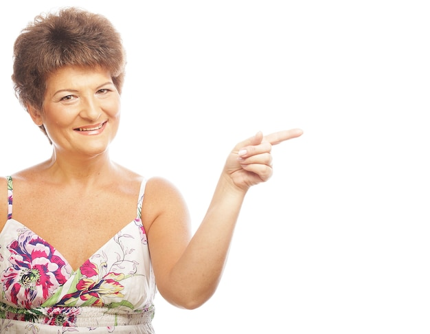 Donna matura che indica sopra lo spazio bianco