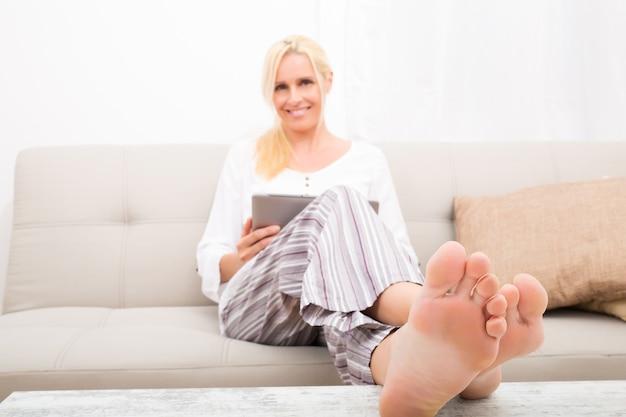 Una donna matura in pigiama con un tablet pc sul divano. concentrati sulle dita dei piedi.
