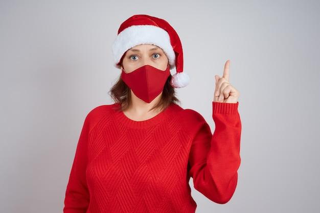 Una donna matura con una maschera protettiva rossa, un cappello da babbo natale su uno sfondo grigio, mostra un gesto di attenzione. natale, capodanno in quarantena.