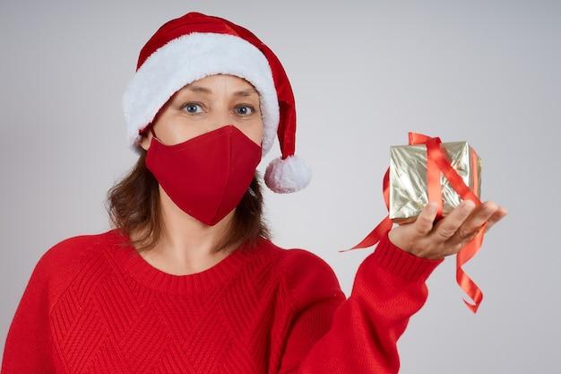 Donna matura in maschera protettiva rossa, in santa cappello su sfondo grigio con confezione regalo. natale, capodanno in quarantena.