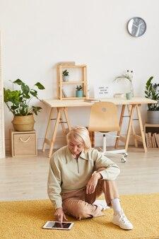 Donna matura che riposa sul pavimento guardando la tavoletta digitale e sorridente nel soggiorno di casa