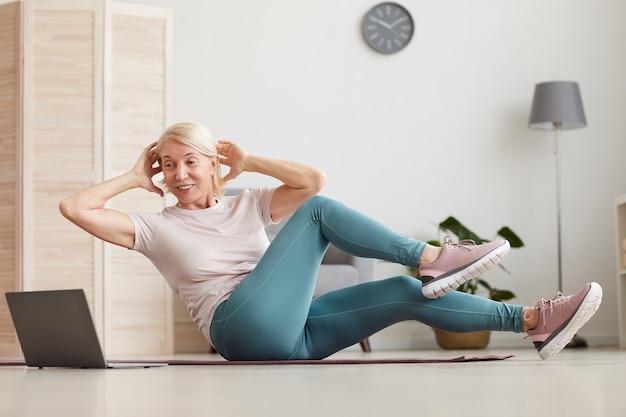 Donna matura che si siede sulla stuoia di esercizio e facendo esercizi lei guarda l'allenamento sportivo online sul laptop mentre è seduto a casa