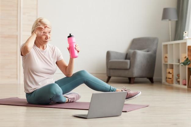 Donna matura che si siede sul pavimento sulla stuoia di esercizio e sull'acqua potabile dopo l'allenamento sportivo a casa