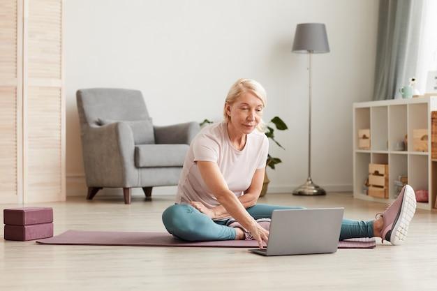 Donna matura seduta sul pavimento e utilizzando il computer portatile durante l'allenamento sportivo a casa