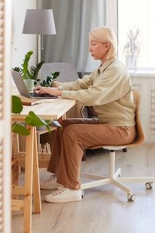 Donna matura che si siede al suo posto di lavoro a casa e che lavora al computer portatile