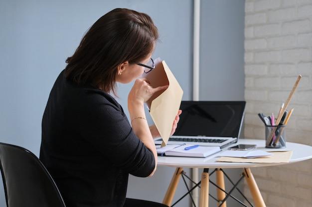 Donna matura seduta a casa alla scrivania con laptop, femmina che guarda in una busta con documenti cartacei