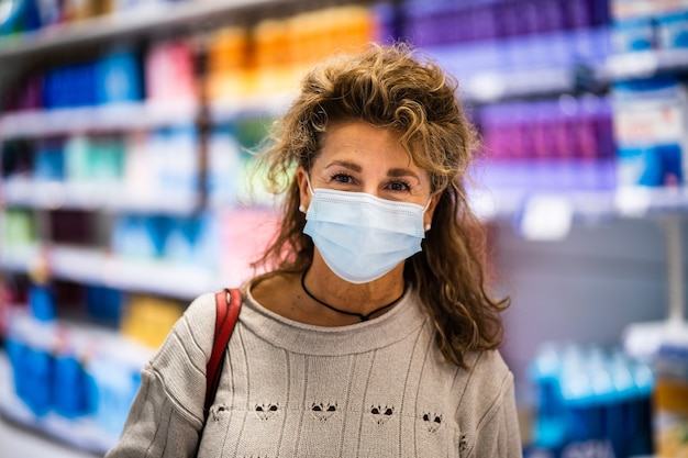Donna matura che sorride alla macchina fotografica mentre indossa la maschera in supermercato