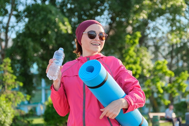 Donna matura in giacca a vento sportiva con stuoia di yoga bottiglia d'acqua, passeggiate all'aperto. stile di vita sano e attivo, sport, fitness nelle persone di mezza età