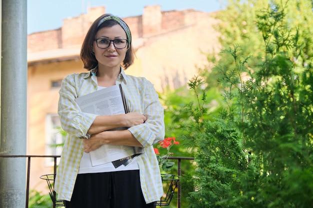 Donna matura in piedi sul balcone aperto in isolamento, rivista di lettura femminile da sola, messa in quarantena durante l'infezione virale, copia spazio