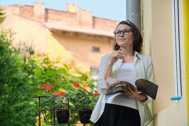 Donna matura in piedi sul balcone aperto in isolamento, rivista di lettura femminile da sola, messa in quarantena durante l'infezione virale