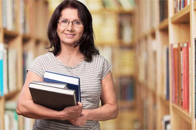 Insegnante donna matura con libri sullo sfondo