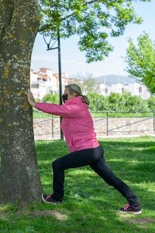 Una donna matura si allena in un parco facendo stretching indossando una maschera chirurgica durante la pandemia di covid