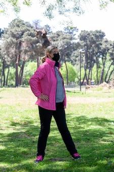 Una donna matura si allena in un parco facendo stretching mentre ascolta musica o un podcast