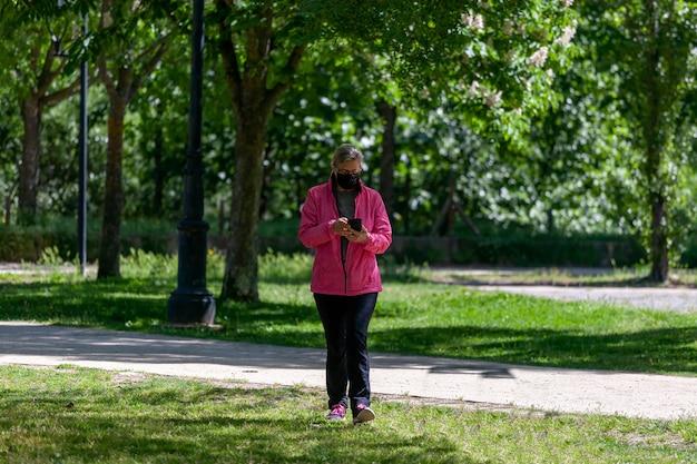 Una donna matura si allena camminando in un parco mentre consulta i social network sul suo telefono