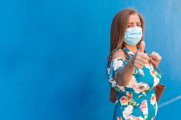 Donna matura che indossa una maschera protettiva e mostra il pollice in su