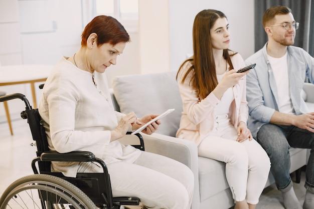 Donna matura in sedia a rotelle guarda la tv con i suoi figli adulti. prendersi cura delle persone disabili.