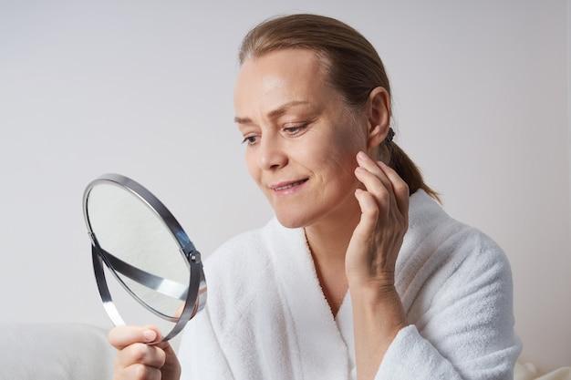 Una donna matura in una vestaglia bianca si guarda allo specchio. cura della pelle domestica per la pelle più anziana.
