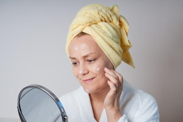Una donna matura in una vestaglia bianca da mattina, con un asciugamano giallo in testa, si guarda allo specchio e si applica una crema sul viso. cura della pelle a casa in età avanzata.