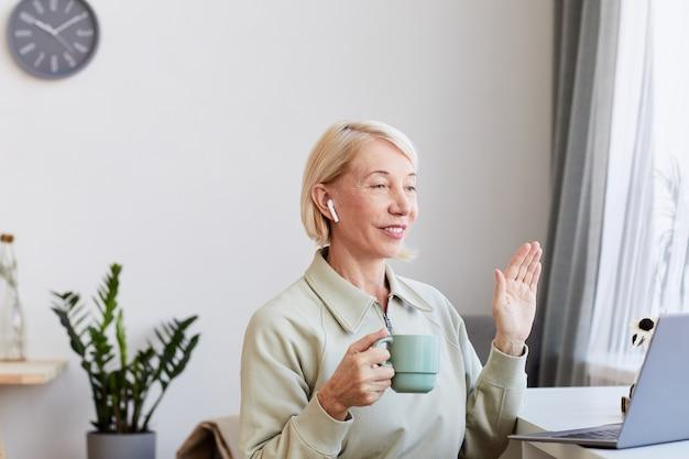 Donna matura con capelli biondi, bere caffè e comunicare online utilizzando il suo laptop a casa