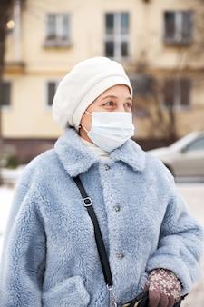 Donna matura con protezione maschera facciale, donna anziana in maschera facciale a causa dell'inquinamento atmosferico nella città di sera, anziani malati con mascherina medica. inquinamento, allergia alla polvere e concetto di salute