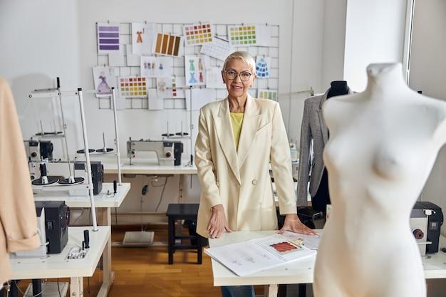 Donna matura con gli occhiali sta al tavolo con disegni di vestiti nel laboratorio di cucito