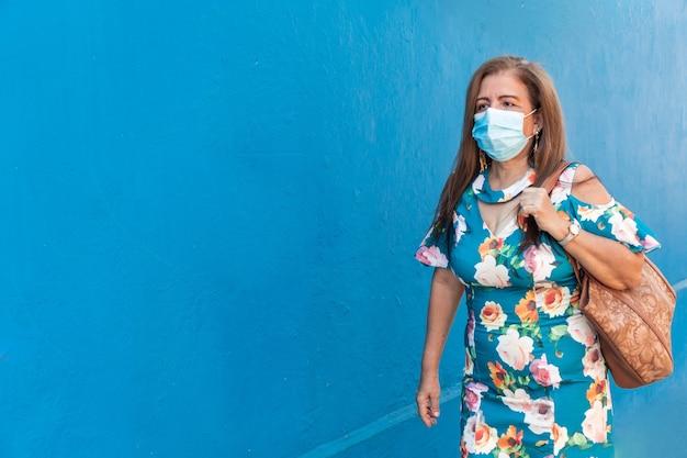 Donna matura con maschera protettiva che cammina per strada